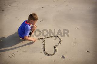 Junge zeichnet am Sandstrand