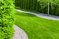 Well maintained formal garden with a path of small stones, hedgerow and green lawn