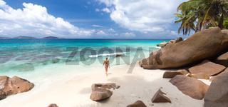 Woman enjoying Anse Patates picture perfect beach on La Digue Island, Seychelles.