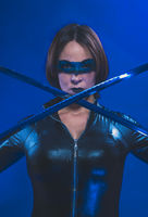 Brunette girl dressed in leather and latex fitted with japanese swords on blue background