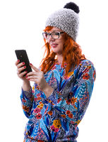 Portrait of a smiling hipster red hair girl reading messages or watching video on mobile phone, isol