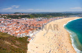 Bird's-eye view on Nazare beach riviera on the coast of Atlantic ocean with Nazare town