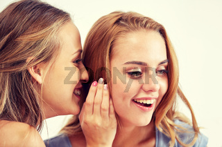 happy young women whispering gossip at home