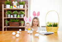 Easter concept. Happy mother and her cute child wearing bunny ears getting ready for Easter