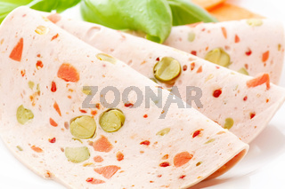 Rolled Paprika Lyoner with basil and carrot as closeup on a white plate