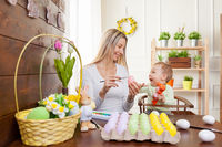 Easter concept. Happy mother and her cute child getting ready for Easter by painting the eggs