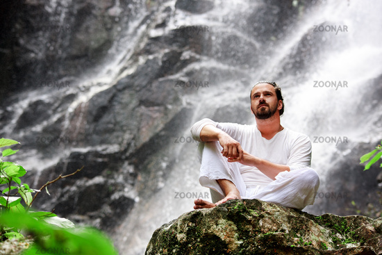 Man sitting in meditation yoga on rock at waterfall in tropical