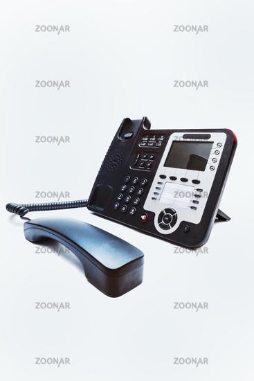 Black IP office phone closeup on white background