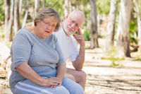 Upset Senior Woman Sits With Concerned Husband Outdoors