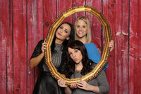 3 girls look through a golden frame and have fun