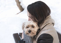 Girl holding a dog in her arms