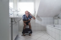 Man, senior, sitting on the toilet and the phone with a smartphone.