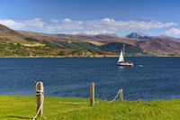 Sailing yacht at sea with mountain range in the background and grassy seashore in the foreground