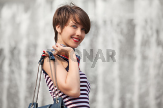 Happy young fashion woman with handbag walking outdoor