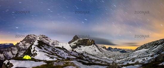 Panaorma of illuminated tent under starry night sky in snowy alpine mountains. Alps, Switzerland.