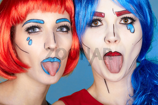 Females in red and blue wigs on blue background. Girls show each other tongues