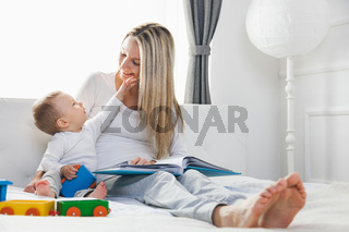 Child education. Happy mother with her toddler sitting on the bed and reading a book together