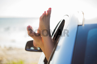 close up of woman feet showing from car window