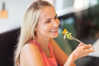 happy young woman eating at restaurant