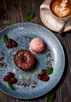 Molten chocolate cake (Chocolate fondant cake / lava cake). Served with ice cream, cherry berries and cup of cappuccino.