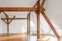empty loft room with wooden framework and parquet floor