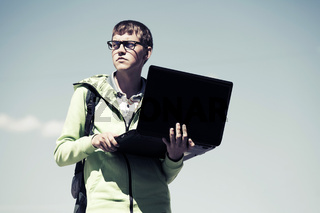 Young man using laptop outdoor
