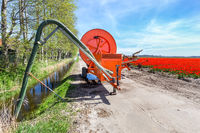 Spraying equipment on road near ditch and tulips