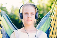 Cute girl listening to music with headphones outdoor - looking at camera