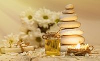 Chamomile essential oil, bouquet of chamomile flowers, stack of rocks and candle