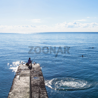 fisher on pier and swimming tourists in Black Sea