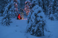 Man beside a campfire in a snowy forest, Lapland, Sweden