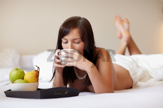 Young beautiful woman drinking coffee lying on white bed