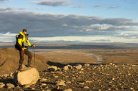 Man standing on mountain rock in dramatic illuminated landscape panorama in Iceland. View to Kjolur Highland and Hekla Volcano.
