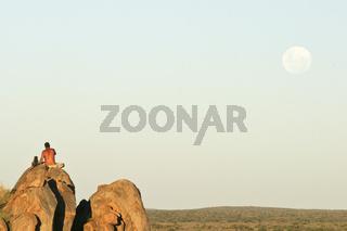 Namibianischer Mann und junger zahmer Steppenpavian, Pavian (Papio cynocephalus) sitzen auf einem Felsen und beobachten den Mondaufgang, Namibia, Afrika, Man with tame Yellow Baboon watches moonrise, Africa