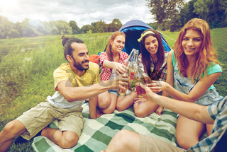 happy friends with tent and drinks at campsite