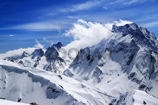 Winter mountains with snow cornice and blue sky with clouds in nice sun day