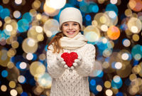 happy girl in winter clothes with red heart