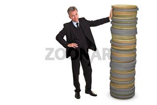 Geschäftsmann lehnt an Stapel Münzen