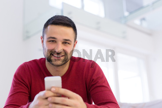young man using a mobile phone  at home