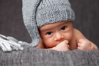 Beautiful newborn baby wearing a cute grey hat