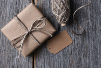 Top view of a plain wrapped Christmas present on a rustic wood table with twine and a blank tag.