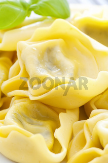 Boiled tortellini with basil as closeup on a white plate