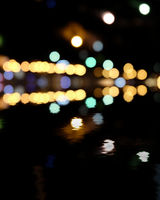 Blurred city at night, bokeh background. Yellow and green spots on black