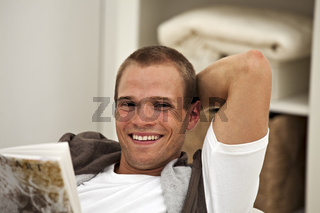 smiling young man reading a book