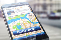Booking hotel by smartphone. Mobile phone with map of the city and proposals for appartment reservation.