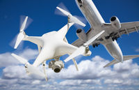 Unmanned Aircraft System (UAV) Quadcopter Drone In The Air Too Close To Passenger Airplane.