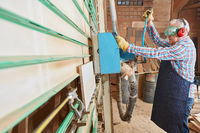 Senior sägt Holz mit Plattensäge