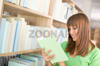 Student in library - happy woman read book