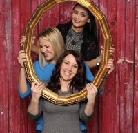 3 girls look through a golden frame and laugh