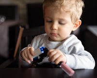 Infant boy plays with objects at restaurant